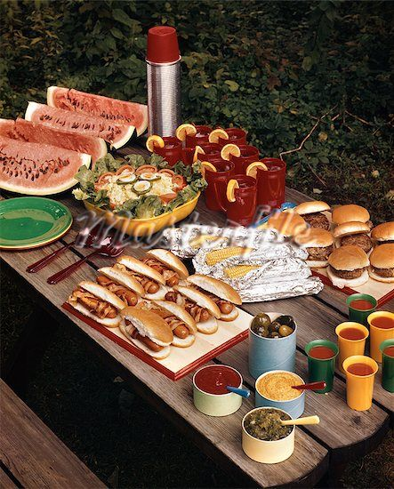 846-03164282 © ClassicStock / Masterfile Model Release: No Property Release: No 1950s PICNIC TABLE TOP FULL OF FOOD CORN HOT DOGS HAMBURGERS WATERMELON SALAD THERMOS CONDIMENTS BACKYARD SUMMER MEAL